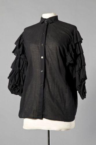 LOT comprenant un CHEMISIER en coton tissé noir agrémenté de demi-manches  ornées de volants superposés (T 38) et une BLOUSE en dentelle anglaise  blanche, ... 46352bcda1b