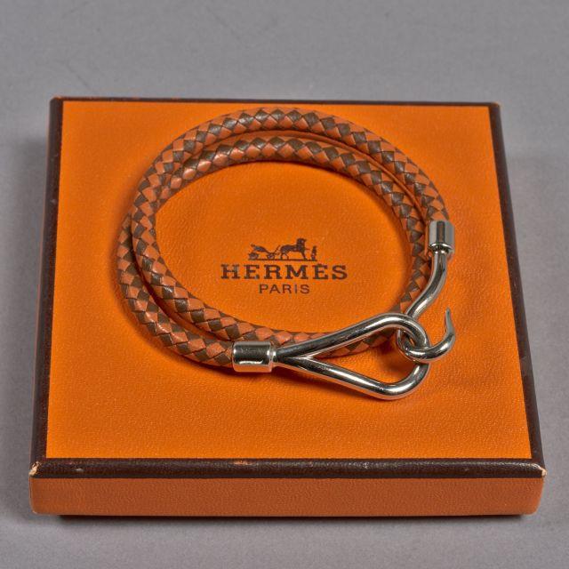 17af83572ff7 HERMES, Bracelet jumbo double tour en métal doré et cuir tressé marron et  orange.