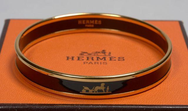 HERMES, Bracelet rigide en métal doré émaillé noir à décor de la Calèche.  Diam 80cdc18ca02