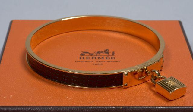 HERMES, Bracelet rigide en cuir noir, garniture en métal doré, orné du  célèbre c47ec5b5693
