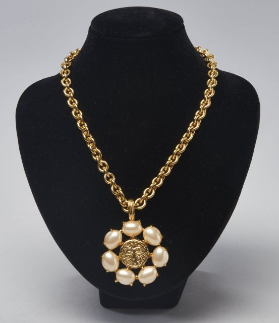 3572940649f5 CHANEL, Pendentif circulaire en métal doré agrémenté de sept perles  bourgeoises, médaillon central à