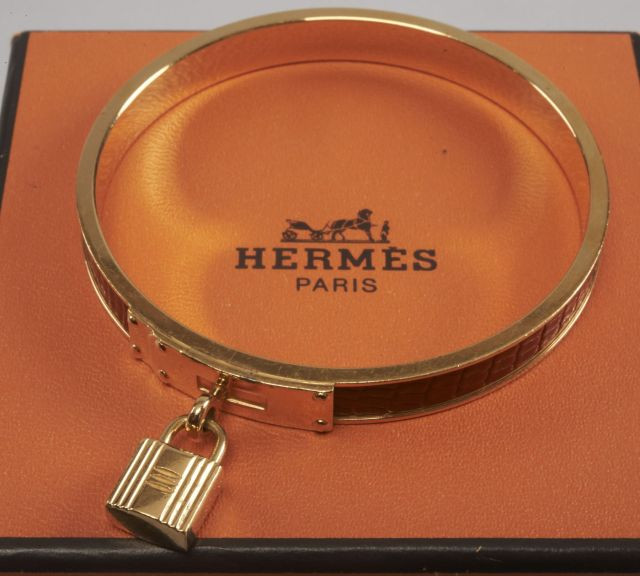 HERMES, Bracelet jonc en lézard rouge et métal doré orné du célèbre cadenas  de la 40295965772