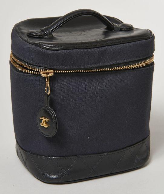 CHANEL, Trousse de toilette en toile et cuir partiellement matelassé noir.  Poignée de portage c4ecd57fdff3